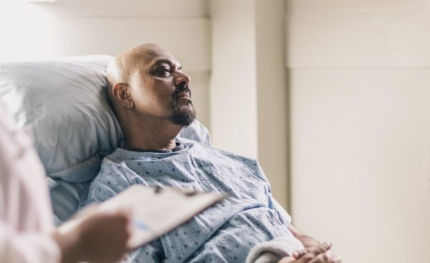 doctor with chart talks to man in hospital bed